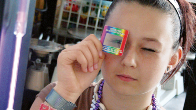 middle school science student looks through prism