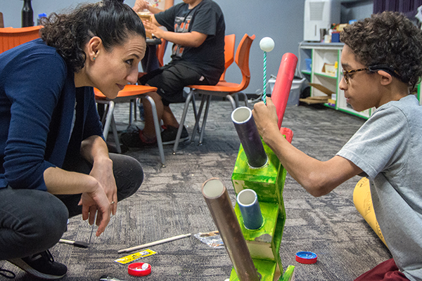 Shirin Vossoughi crouches so her gaze is at eye level with a student.